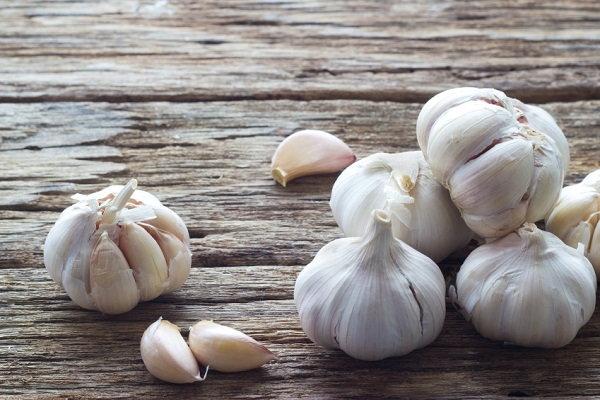 Garlic gloves on wood surface