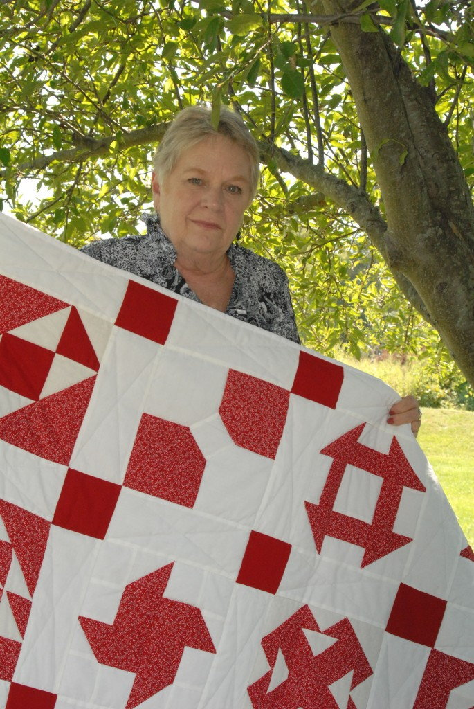 woman holding red and white quilt