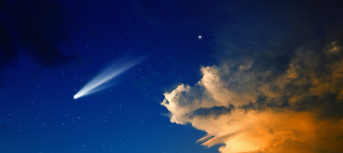 comet in night sky with clouds