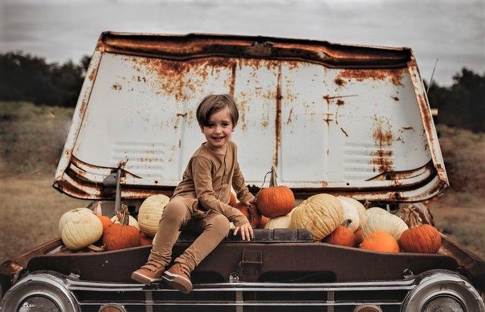 little boy sitting on a pile of pumpkins
