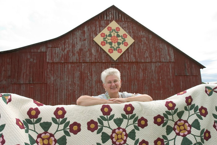 quilter with quilt that matches her barn