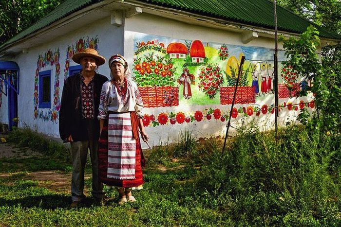 Russian couple with colorful painted house