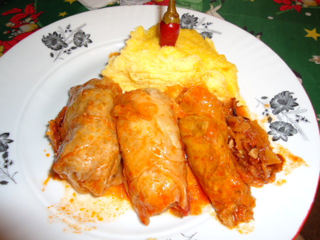 Three pork stuffed cabbage rolls with polenta and a hot pepper in it