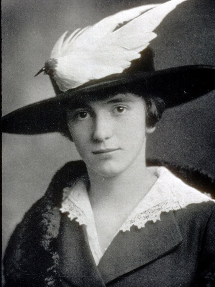 portrait of woman with bird wing on hat