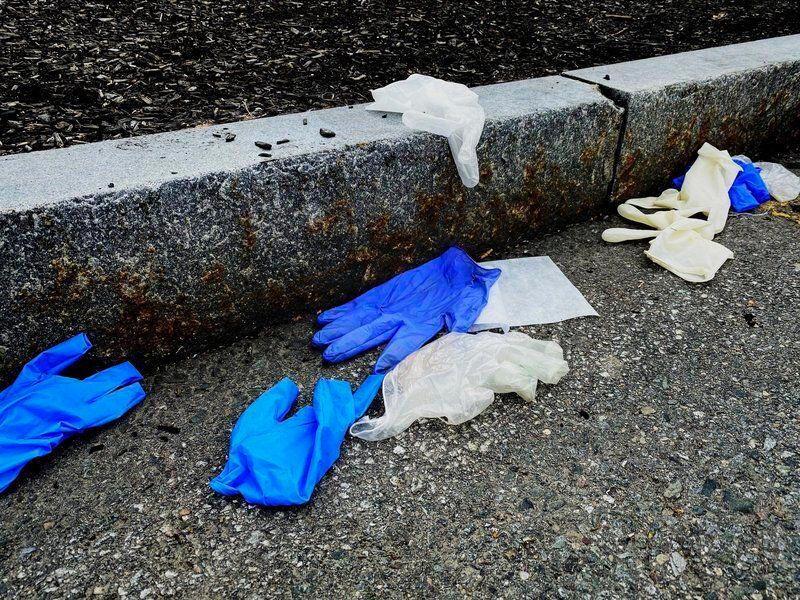 surgical gloves littering a sidewalk