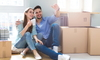 A couple on moving day sitting on the floor surrounded by boxes.