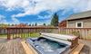 A hot tub on a backyard deck, still half covered.