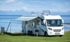 an RV by the water with an awning