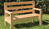 A completed wooden bench outside on the lawn.