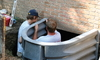 Two men install egress window wells.