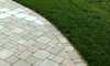 Grass borders a driveway made from pavers.