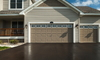 A fresh asphalt driveway in front of an attached garage.