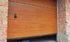 wooden roll-up garage door between brick columns