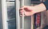 A person opening a refrigerator door.