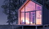 beautiful tiny house on the water at night with a glass front wall