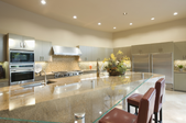 a large kitchen with huge island and rows of recessed lighting.