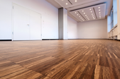 large room with bamboo flooring and white walls