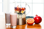 A blender with fruit and yogurt inside for smoothies.