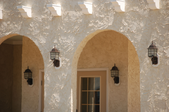 The front of a building with arched walkways and stucco wall