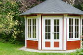 Red and white gazebo encased with windows