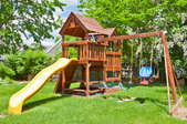 A wooden playset in a private backyard.