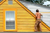 a man paints the outside of the second story of a house yellow