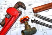 A wrench and some pipes laying on top of blueprints.