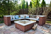 A patio with a brick firepit and bench.