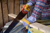 Man cutting a board with a handsaw