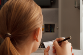 woman taking notes while looking at a fuse box