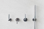 3-handle shower faucet on a shower wall