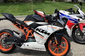 two motorcycles. in the foreground, an orange and white motorcycle, in the background a red, white, and blue motorcycle