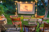 Chairs on a lawn in front of an outdoor movie screen