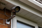 security camera mounted to the side of the house.