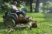 A man using a riding lawn mower.