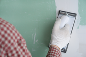 man mudding a seam on the wall