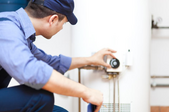 repairman adjusting temperature on a water heater