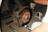 A person works on a brake rotor.