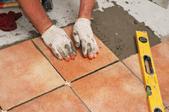 installing ceramic tile on the floor.