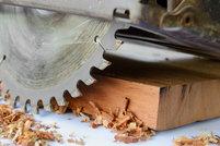 A circular saw cutting a wood plank.