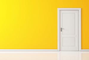 A white, interior door set into a yellow wall.