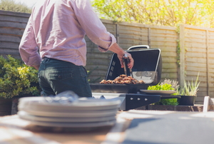 A man grilling on a barbecue with a stack of plates in the foreground.