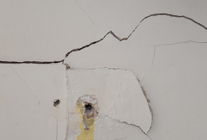 A wall with a large crack and hole.