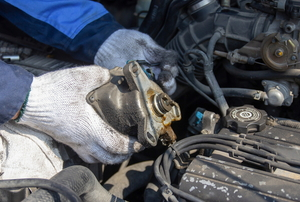 gloved hands working with a car engine ignition system under the hood