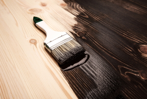 A brush laying on top of a wooden table being varnished.