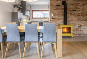dining room with exposed brick, woodstove, and upholstered chairs at a long table