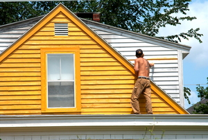 a triangular yellow house with a person standing on the roof