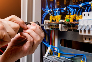 A technician works on a circuit breaker.