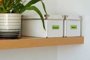 Floating, corner shelves with storage boxes and a houseplant.
