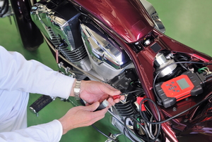 A person performing basic maintenance on a red motorcycle.